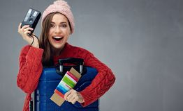 Happy tourist woman wearing winter clothes ready for travel with. Suitcase and camera. Gray wall back Stock Images