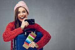 Happy tourist woman wearing winter clothes ready for travel with. Suitcase and camera. Gray wall back Royalty Free Stock Images