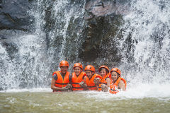 Happy tourists abseil in Datanla waterfall, Vietnam. DALAT, VIETNAM - JULY 28, 2014: Unidentified Caucasian young women tourists having abseiled in Datanla Stock Image
