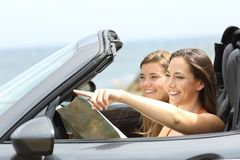 Happy tourists in a car consulting guide on vacations Stock Images