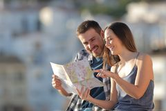 Happy tourists checking guide in a town on vacation. Couple of happy tourists checking paper guide in a town on vacation stock photo