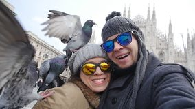 Happy tourists with doves in front of Duomo cathedral, Milano. Happy tourists taking a self portrait with phone in front of Duomo cathedral,Milan - Couple stock video