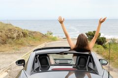 Happy tourists driving a convertible car on vacation. Back view portrait of two happy tourists driving a convertible car on vacation stock photography