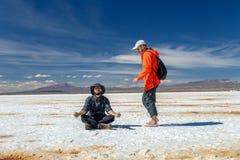 Happy tourists enjoy Jeep tour activities in Salt flats Salar de Uyuni in Bolivia. Salar de Uyuni, Uyuni, Bolivia – April 2019 : Tourists walk stock images