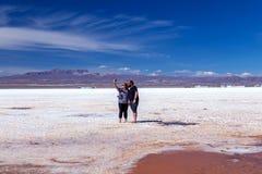 Happy tourists enjoy Jeep tour activities in Salt flats Salar de Uyuni in Bolivia. Salar de Uyuni, Uyuni, Bolivia – April 2019 : Tourists walk royalty free stock photography