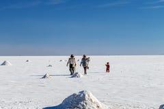 Happy tourists enjoy Jeep tour activities in Salt flats Salar de Uyuni in Bolivia. Salar de Uyuni, Uyuni, Bolivia – April 2019 : Tourists walk royalty free stock photos