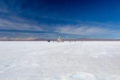 Happy tourists enjoy Jeep tour activities in Salt flats Salar de Uyuni in Bolivia. Salar de Uyuni, Uyuni, Bolivia – April 2019 : Tourists walk royalty free stock image