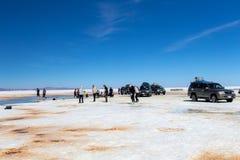Happy tourists enjoy Jeep tour activities in Salt flats Salar de Uyuni in Bolivia. Salar de Uyuni, Uyuni, Bolivia – April 2019 : Tourists walk royalty free stock photo