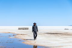 Happy tourists enjoy Jeep tour activities in Salt flats Salar de Uyuni in Bolivia. Salar de Uyuni, Uyuni, Bolivia – April 2019 : Tourists walk stock image