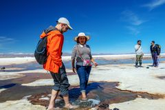 Happy tourists enjoy Jeep tour activities in Salt flats Salar de Uyuni in Bolivia. Salar de Uyuni, Uyuni, Bolivia – April 2019 : Tourists walk stock photos