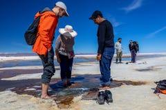 Happy tourists enjoy Jeep tour activities in Salt flats Salar de Uyuni in Bolivia. Salar de Uyuni, Uyuni, Bolivia – April 2019 : Tourists walk stock photo