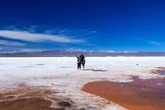 Happy tourists enjoy Jeep tour activities in Salt flats Salar de Uyuni in Bolivia. Salar de Uyuni, Uyuni, Bolivia – April 2019 : Tourists walk royalty free stock images
