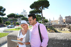 Happy tourists holding tablet during visit of Rome. Couple of tourists using tablet to visit Rome Capital Stock Photos