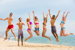 Happy tourists jumping on beach Royalty Free Stock Image