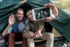 Happy tourists making selfie on smartphone in tent royalty free stock image