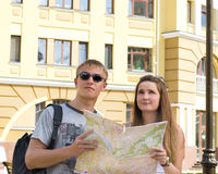 Happy tourists with a map. Happy young tourists with a map looking up at a landmark that they have just pin pointed the locality of on the map Stock Photos