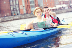 Happy tourists with a map in a canoe. A picture of a young couple with a map in a canoe Royalty Free Stock Photo