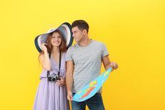 Happy tourists with map. On color background Royalty Free Stock Images