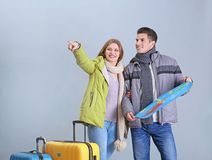 Happy tourists with map. On grey background Stock Photography