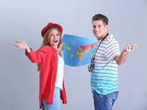 Happy tourists with map. On grey background Stock Photo