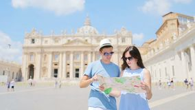 Happy couple tourists with map background St. Peter`s Basilica church in Vatican city, Rome, Italy.