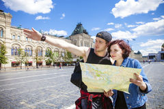 Happy tourists sightseeing city with map Stock Images