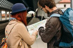 Happy tourists sightseeing city with map on train station before walking or travelling. Happy tourists sightseeing city with map on train station before walking Stock Photo