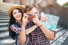 Happy tourists stand outside and pose. She smiles and embrace her boyfriend. He takes pictures by holding camera in stock images