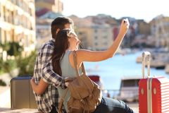 Happy tourists takig selfies on summer vacation. Happy tourists takig selfies sitting in a port on summer vacation Royalty Free Stock Photos
