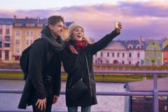 Happy tourists taking photo of themselves on smartphone. Holidays, travel, vacation, tourism and dating concept. Weeknd in Europe. In valentines day. Pretty royalty free stock photo