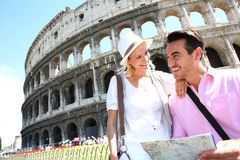 Happy tourists visiting Coliseum with map. Tourists reading map in front of the Coliseum, Rome Royalty Free Stock Photography
