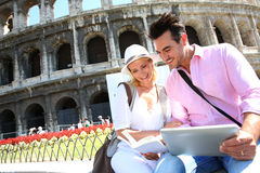 Happy tourists visiting Coliseum with tablet Stock Images