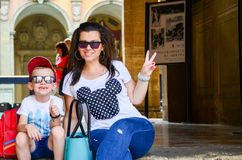 Happy tourst near Bologna`s univesity. Smiling Mother and son sitting on upstairs near the  university of  the historic city of  Bologna , Italy Stock Photo