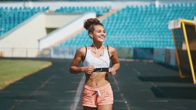 Portrait of a strong fit girl in sportswear running in the stadium. Beautiful girl runs in the stadium and listens to. Happy track running girl runner listening stock video