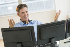 Happy Trader Gesturing While Using Multiple Screens At Desk. Happy mature male trader gesturing while using multiple screens at desk in office stock images