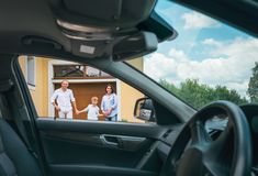 Happy traditional family near their house portrait who bought new car. Inside car view stock photography