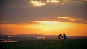 Happy traditional family walking outdoor - mom, dad and little son - to sunset at summer meadow