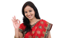 Happy traditional Indian woman making ok gesture. Against white Stock Photos