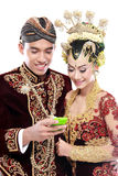 Happy traditional java wedding couple with mobile phone Royalty Free Stock Photo