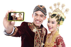 Happy traditional java wedding couple with mobile phone Royalty Free Stock Images