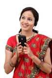 Happy traditional woman listening to music from a cellphone Stock Photo