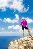 Happy trail runner looking at inspirational landscape. Accomplished runner, climber or hiker business concept. Woman trail runner looking at beautiful stock image