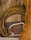 Happy trails wood shelf with rope & chaps. Western theme rawhide lariat on old wood shelf with leather chaps and Happy Trails sign Stock Image