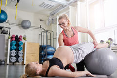 Happy trainer helping pregnant woman doing stretching exercises. Portrait of happy trainer helping pregnant women doing stretching exercises Stock Photo