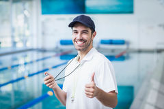 Happy trainer holding stopwatch with thumbs up Stock Images