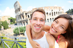 Happy travel couple in piggyback by Coliseum, Rome. Italy. Smiling young romantic couple in love traveling in Europe having fun together in front of Colosseum Royalty Free Stock Photography