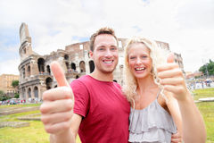 Happy travel couple in Rome by Coliseum in love. Happy Travel couple in Rome by Coliseum showing thumbs up hand sign looking at camera cheerful. Two tourists Stock Photography