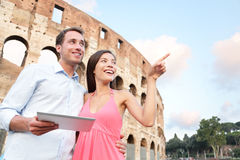 Happy travel couple with tablet by Coliseum, Rome Stock Image