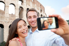 Happy travel couple taking selife, Coliseum, Rome. Happy travel couple taking selife by Coliseum, Rome, Italy. Smiling young romantic couple traveling in Europe Stock Photography