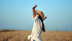 Happy travel female in white shirt rising hand enjoying freedom surrounded by wheat field. Medium shot. Smiling fashion woman in sunglasses and hat relaxing stock video